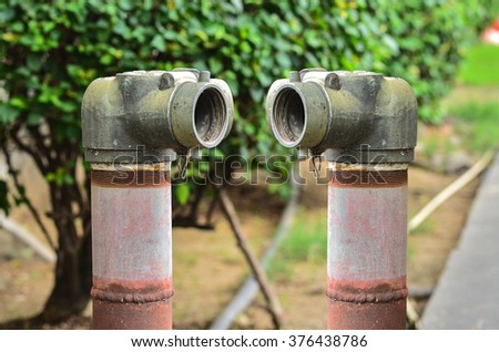 Two Close up red fire hydrant near wall - stock photo