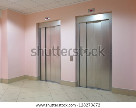Two closed modern elevators in a business lobby - stock photo