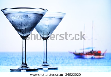 Two cocktail glasses and sea in the background - stock photo