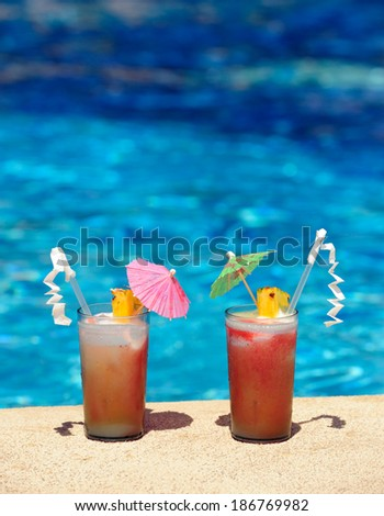 Two cocktail glasses by a blue water of swimming pool  (your text on top of the image)  - stock photo