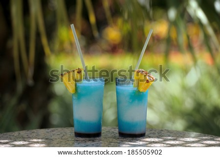 Two cocktail glasses on marble table and green background - stock photo