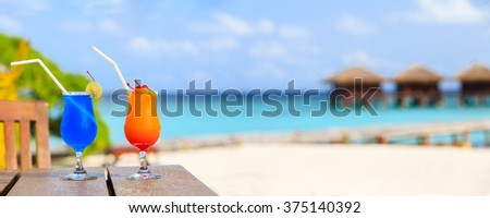 Two cocktails on luxury beach resort, wide panorama - stock photo