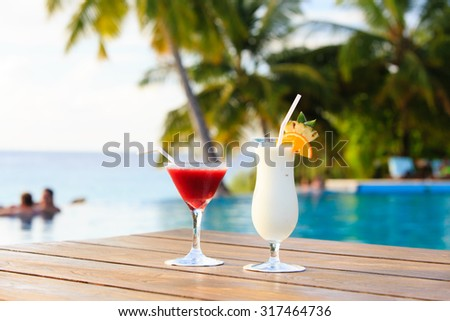 Two cocktails on luxury tropical beach vacation - stock photo