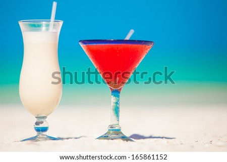 Two cocktails: pina colada and strawberry margarita on white sand beach - stock photo