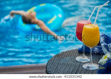 Two cocktails yellow and red beside swimming pool. Woman in swim ring blurred in background. Spa, travel, vacation concept. Text space