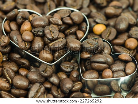 Two coffee beans on in heart shape box closeup macro