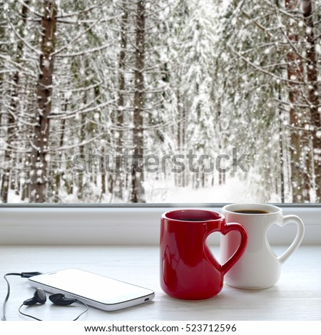 Two coffee cups, smartphone and headphones on a windowsill. In the background, a beautiful winter forest in snow