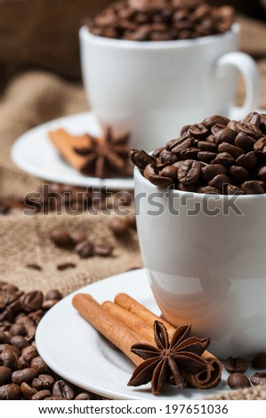 Two coffee cups with coffee beans, aniseed and cinnamon. - stock photo