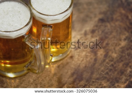 Two cold beer jug on wooden table - stock photo