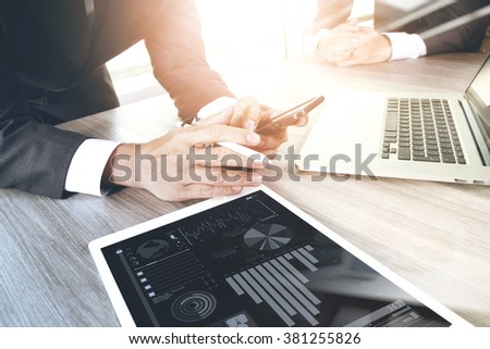 two colleagues businessman discussing data and  digital tablet and computer laptop with smart phone with digital business strategy on wooden desk as concept - stock photo
