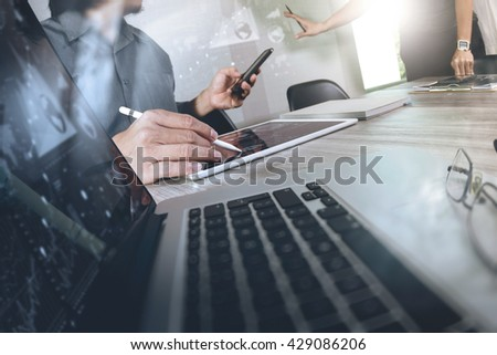 two colleagues businessman discussing data and digital tablet and computer laptop with smart phone with digital business strategy on wooden desk as concept