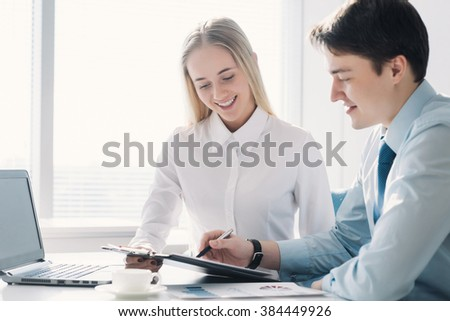 Two colleagues discussing a business project, a man and a woman - stock photo