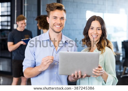 Two colleagues discussing in office on laptop while other two discussing behind them - stock photo