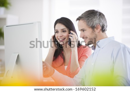 Two colleagues in an office in front of a computer - stock photo