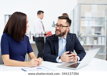 Two colleagues interacting in working environment in office