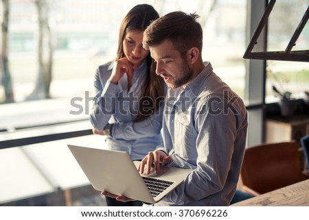 Two colleagues looking at a computer and discussing business. - stock photo