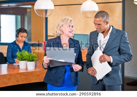 Two colleagues meeting in front of a reception desk where a secretary answers calls to discuss project notes - stock photo