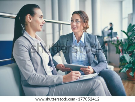 Two colleagues sharing ideas and discussing them at meeting - stock photo