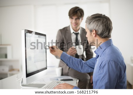 two colleagues speaks about business at office in front of computer - stock photo