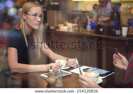Two colleagues with tablets discussing work during lunch in the cafe. - stock photo