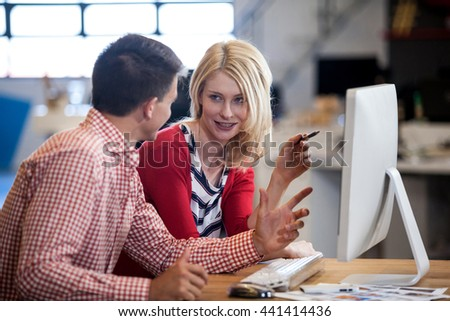 Two colleagues working at computer desk in modern studio - stock photo