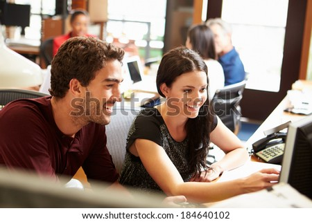 Two Colleagues Working At Desk With Meeting In Background - stock photo