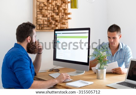 Two colleagues working at office - stock photo