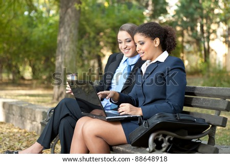 Two colleagues working on laptop and sitting on bench in park - stock photo