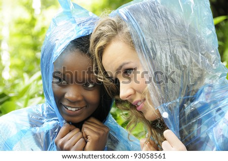 Two college friends getting ready to protect themselves against the rain. - stock photo