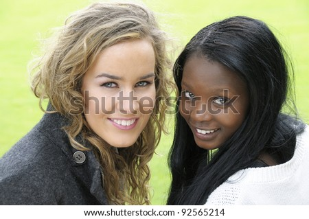 Two college friends sitting on park bench seat. - stock photo