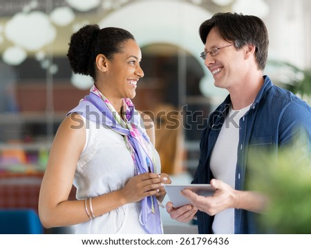 Two collegues standing next to each other in a office - stock photo