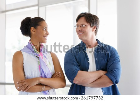 Two collegues standing next to each other in an office