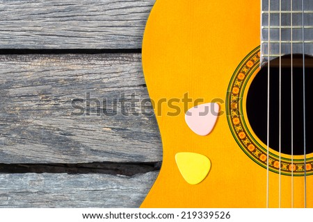 two color picks on acoustic, classical guitar over the old wood texture - stock photo