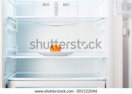 Two-colored orange and red peach on white plate in open empty refrigerator. Weight loss diet concept.  - stock photo
