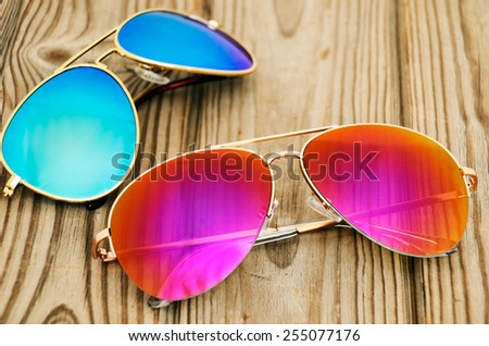 two colored sunglasses on the wooden background. horizontal - stock photo