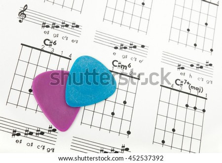 Two colorful guitar picks on a chords chart.