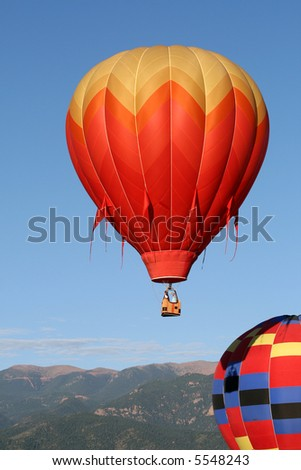 Two colorful hot air balloons during early morning ascend. Mountains in background - stock photo