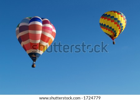 two colorful hot air balloons in flight - stock photo