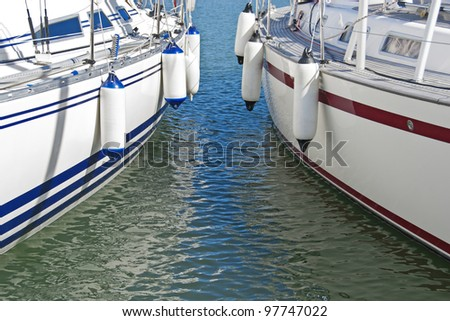 Two colorful motorboats with fenders on calm water parked in the marina. - stock photo