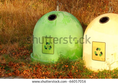 Two colorful recycling bins in a autumn park. - stock photo