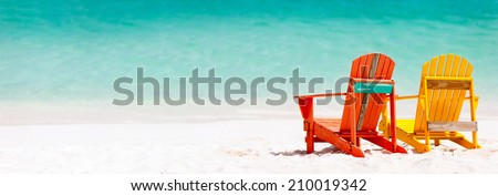 Two colorful wooden chairs at tropical white sand beach in Caribbean, panorama with copy space perfect for banners - stock photo