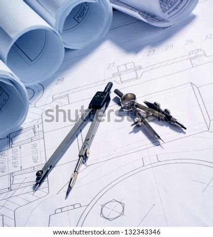 two compasses and rolls of blueprints lying on drawing - stock photo