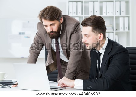 Two concentrated businessmen sitting and standing at office desk discussing business project on laptop - stock photo