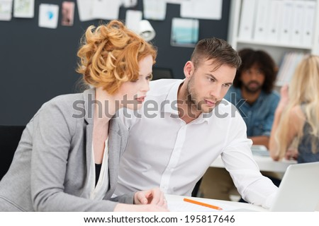 Two concerned young business people, an attractive woman and man, staring at a laptop computer with worried frowns as they sit working at a desk together - stock photo