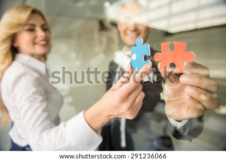 Two confident business people trying to connect small pieces of puzzle at office. - stock photo