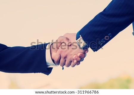Two confident businessman shaking hands - stock photo