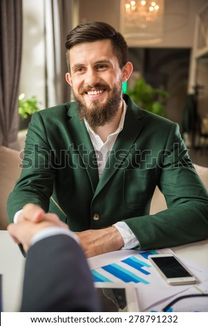 Two confident businessmen discuss contract at business meeting and shaking hands. - stock photo