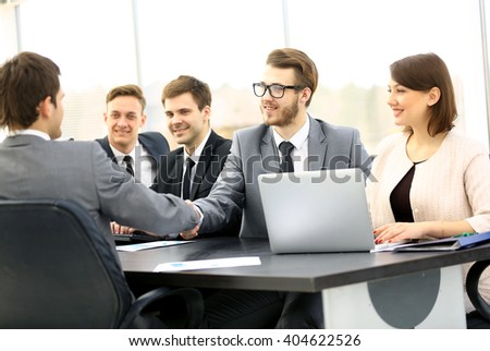 Two confident businessmen handshaking and smiling while sitting at the table together with their colleagues - stock photo