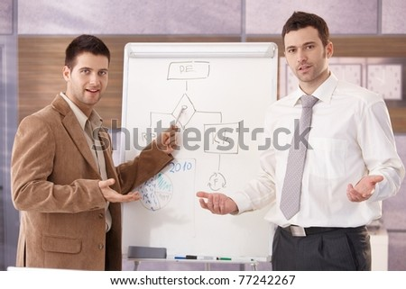Two confident businessmen presenting together over whiteboard, smiling.? - stock photo