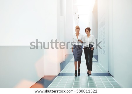 Two confident female leaders reading news on mobile phone about their collaboration while walking together in office, businesswomen watching something on cell telephone while goes in hallway company  - stock photo